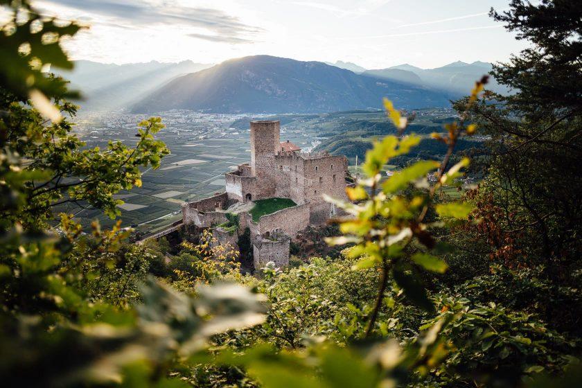 Die Burg Hocheppan bei Sonnenaufgang. Im Hintergrund sieht man die Stadt Bolzano.